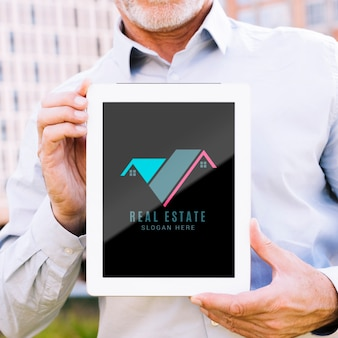 Homme tenant une maquette de tablette avec une entreprise immobilière