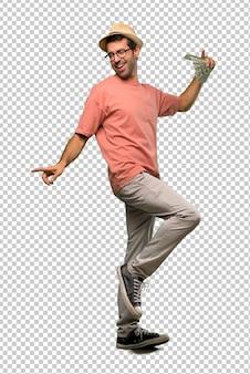 Homme tenant plusieurs billets aiment danser tout en écoutant de la musique lors d'une fête