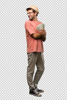 Homme tenant plusieurs billets regardant par-dessus l'épaule avec un sourire