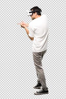 Homme utilisant des lunettes de réalité virtuelle tirant avec un pistolet virtuel