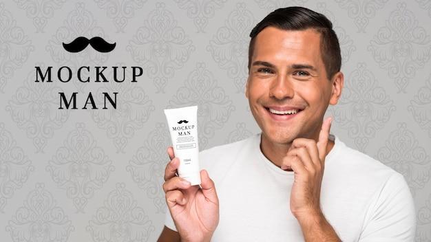 Homme utilisant une maquette de crème pour le visage