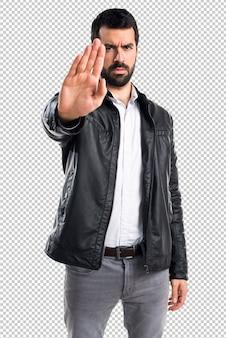 Homme avec une veste en cuir faisant signe d'arrêt