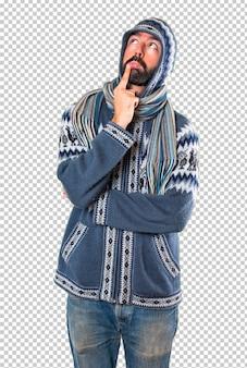 Homme avec des vêtements d'hiver ayant des doutes