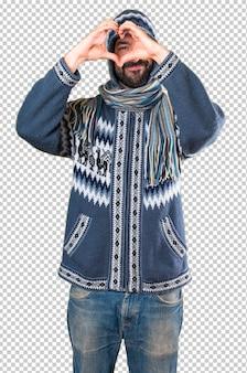 Homme avec des vêtements d'hiver faisant un coeur avec ses mains