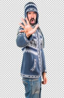 Homme avec des vêtements d'hiver faisant signe d'arrêt