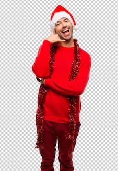 Homme avec des vêtements rouges, célébrant les vacances de noël, faisant un geste de téléphone. rappelle-moi