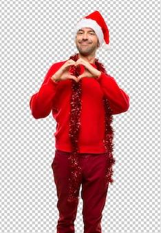 Homme avec des vêtements rouges, célébrant les vacances de noël, faisant le symbole du coeur à la main