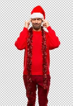 Homme avec des vêtements rouges célébrant les vacances de noël malheureux et frustré par quelque chose