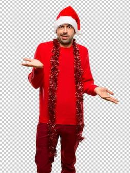 Homme avec des vêtements rouges célébrant les vacances de noël malheureux et frustré avec quelque chose