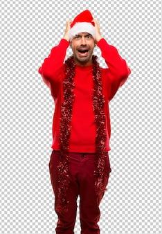 Homme vêtu de vêtements rouges célébrant les vacances de noël prend la tête à cause de la migraine