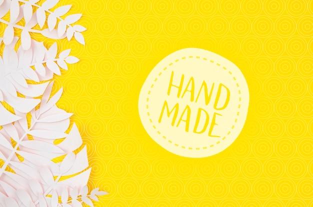 Insigne fait main avec des feuilles blanches sur fond jaune