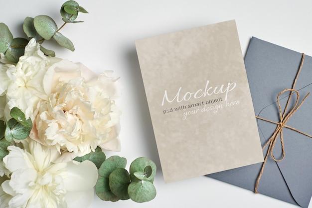 Invitation de mariage ou maquette de carte de voeux avec enveloppe et fleurs de pivoine blanches avec des brindilles d'eucalyptus