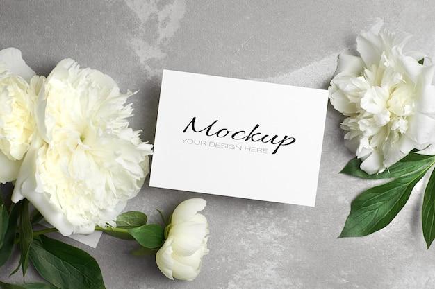 Invitation de mariage ou maquette de carte de voeux avec enveloppe et fleurs de pivoine blanches sur gris