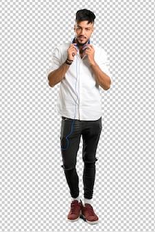 Jeune arabe avec une chemise blanche, écouter de la musique avec des écouteurs
