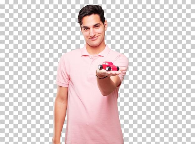 Jeune bel homme bronzé avec un modèle de voiture rouge