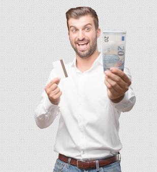 Jeune bel homme avec carte de crédit et facture de 20 euros