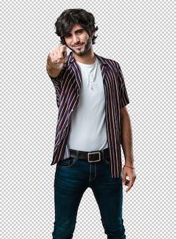 Jeune bel homme gai et souriant pointant vers l'avant