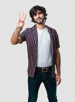 Jeune bel homme montrant le numéro trois, symbole du comptage, concept de mathématiques, confiant et joyeux