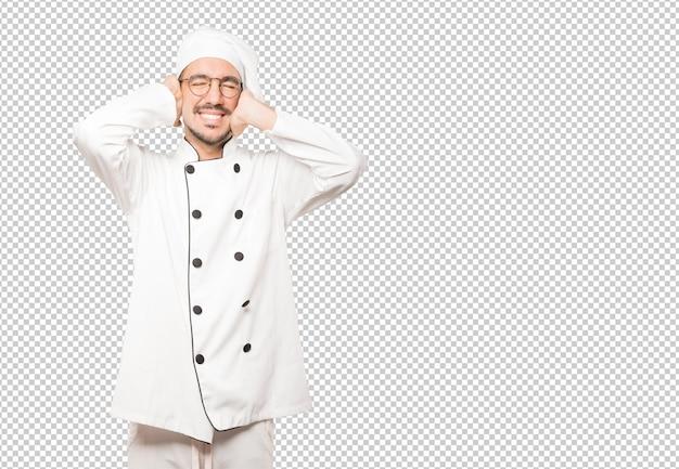 Jeune chef inquiet des bruits forts et couvrant ses oreilles