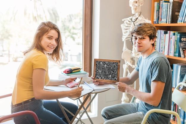 Jeune couple, à, ardoise, maquette, dans bibliothèque