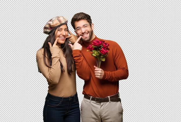 Jeune couple, dans, saint valentin, sourire, pointant bouche