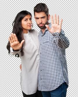 Jeune couple faisant un geste d'arrêt