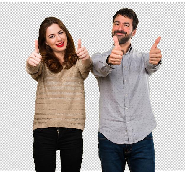 Jeune couple avec le pouce en l'air