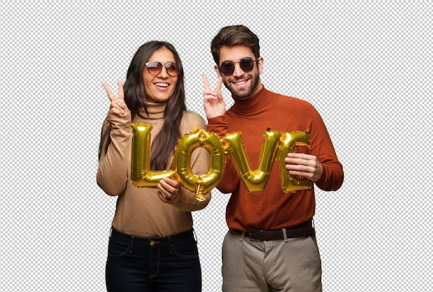 Jeune couple, saint valentin, amusement, heureux, geste victoire