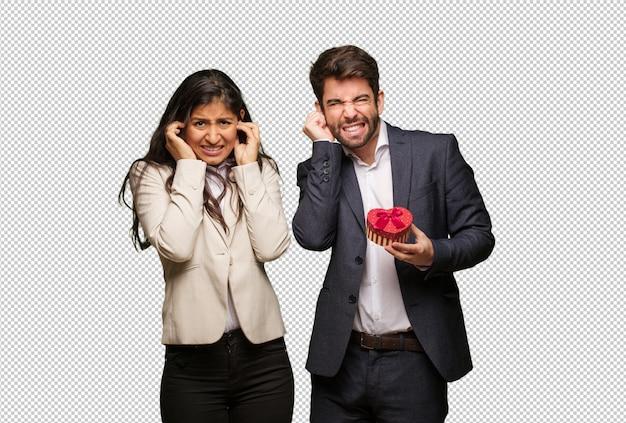 Jeune couple, saint valentin, couvrir, oreilles, à, mains