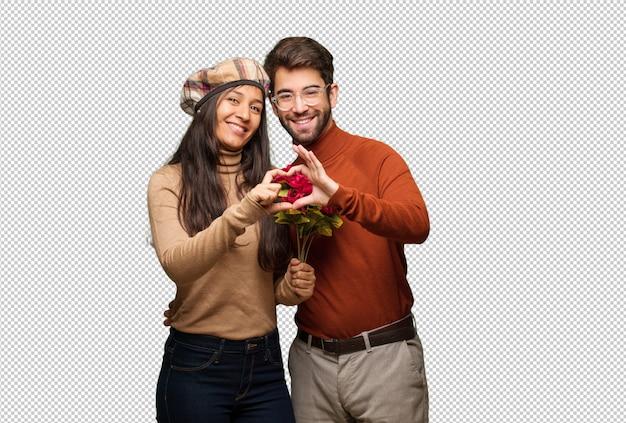 Jeune couple en saint valentin fait une forme de coeur avec les mains
