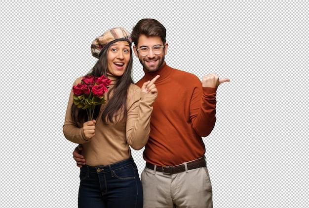 Jeune couple en saint valentin pointant sur le côté avec le doigt