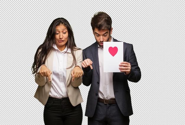 Jeune couple en saint valentin pointant vers le bas