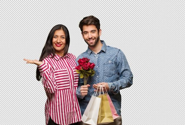 Jeune couple en saint valentin tenant quelque chose avec la main