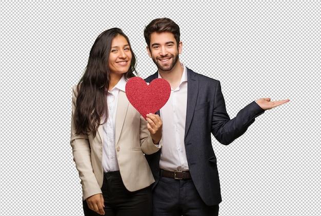 Jeune couple en saint valentin tenant quelque chose avec les mains