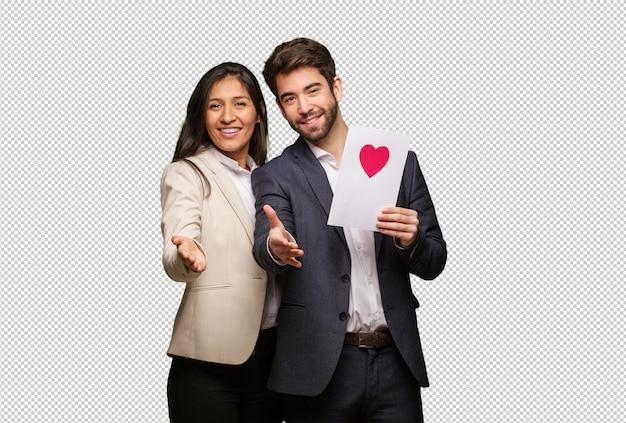 Jeune couple en saint valentin tendre la main pour accueillir quelqu'un