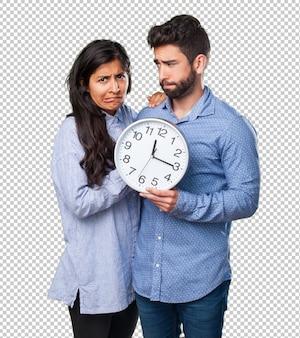 Jeune couple tenant une horloge