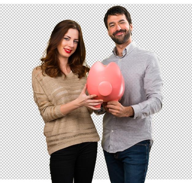 Jeune couple tenant une tirelire