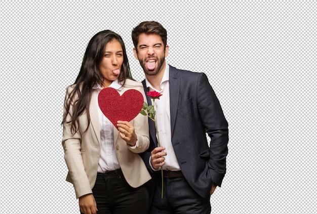 Jeune couple en valentin drôle et amical montrant la langue