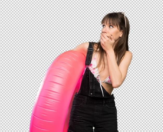 Jeune femme en bikini couvrant la bouche et regardant sur le côté