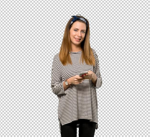 Jeune femme avec foulard envoie un message avec le téléphone portable