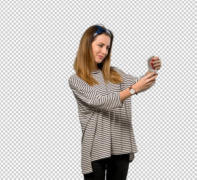 Jeune femme avec foulard faisant un selfie