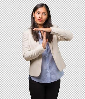 Jeune femme indienne faisant un geste de délai d'attente, notion de temps