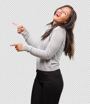 Jeune femme indienne pointant vers le côté