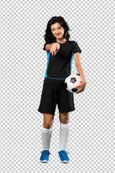 Jeune femme joueur de football pointe un doigt sur vous avec une expression confiante