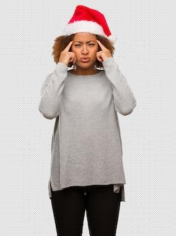 Jeune femme noire coiffée d'un bonnet de noel faisant un geste de concentration