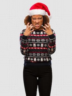 Jeune femme noire dans un pull de noël à la mode avec une impression en colère et contrariée