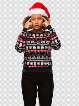 Jeune femme noire dans un pull de noël à la mode avec impression faisant un geste de concentration