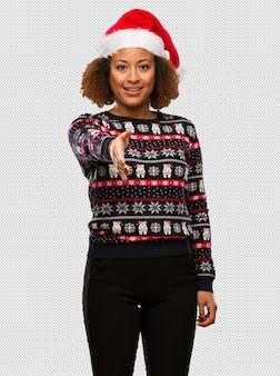 Jeune femme noire dans un pull de noël à la mode avec une impression tendre la main pour saluer quelqu'un