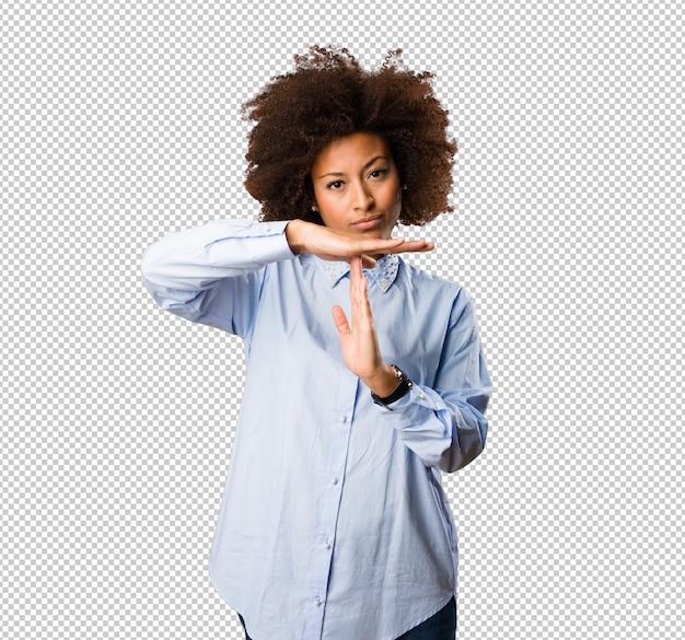 Jeune femme noire faisant le geste de pause