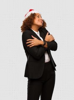 Jeune femme noire portant un bonnet de noel donnant un câlin